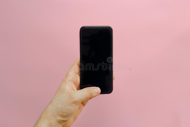 hand holding stylish black phone with empty screen on pink background, flat lay. space for text. modern instagram blogging. royalty free stock images