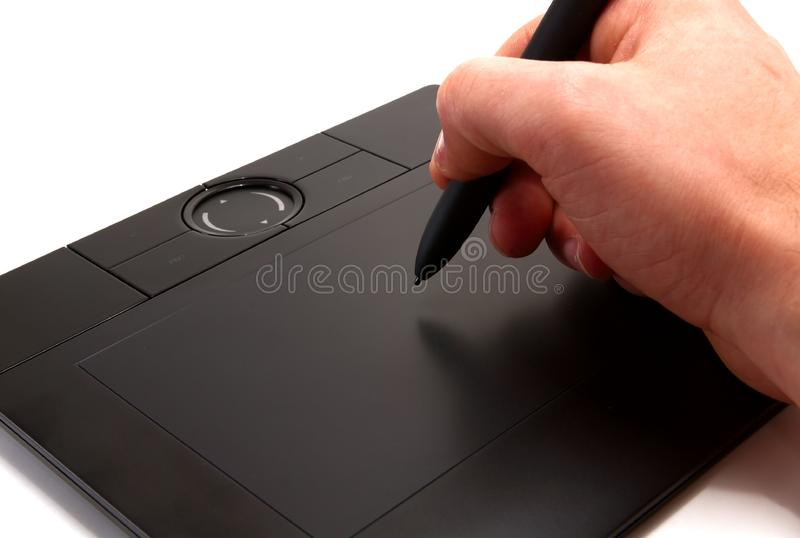 Hand holding stylus on graphics tablet royalty free stock images