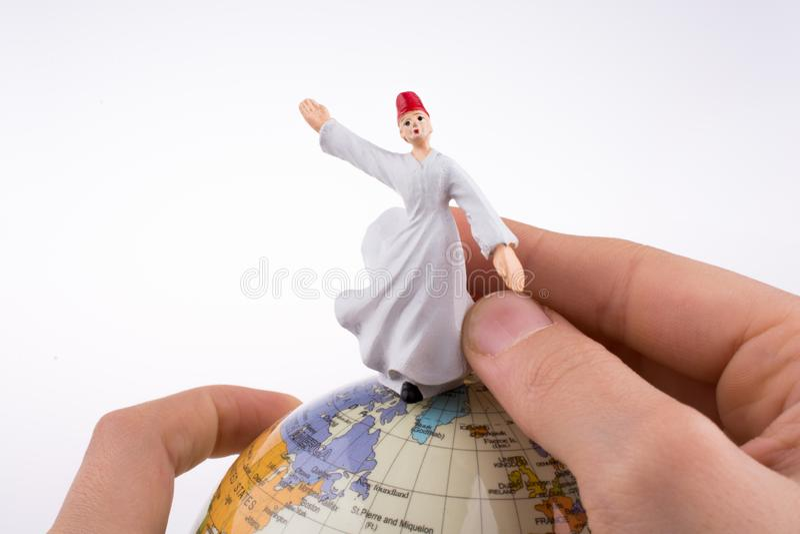 Hand holding a DerviÅŸ on a globe royalty free stock images