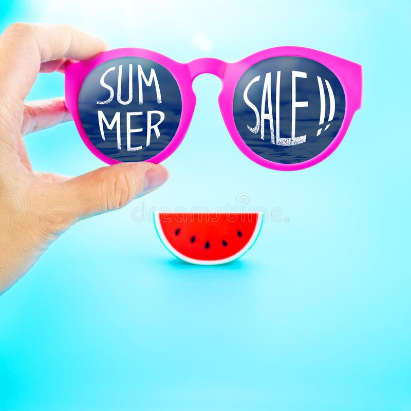 hand holding summer pink glasses with summer sale! word and watermelon at light blue background,Summer Holiday,Leave space for ad royalty free stock image