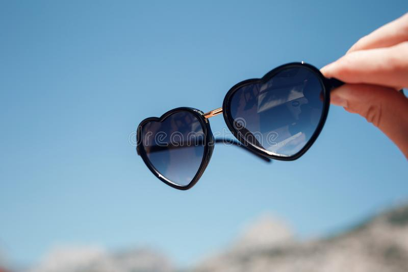 Hand holding sunglasses in shape of heart on a background of blue sky and mountains stock photo