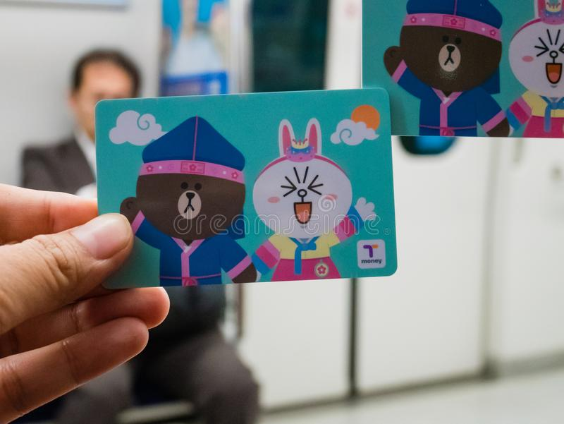 Hand holding T-Money card with Line characters stock photo