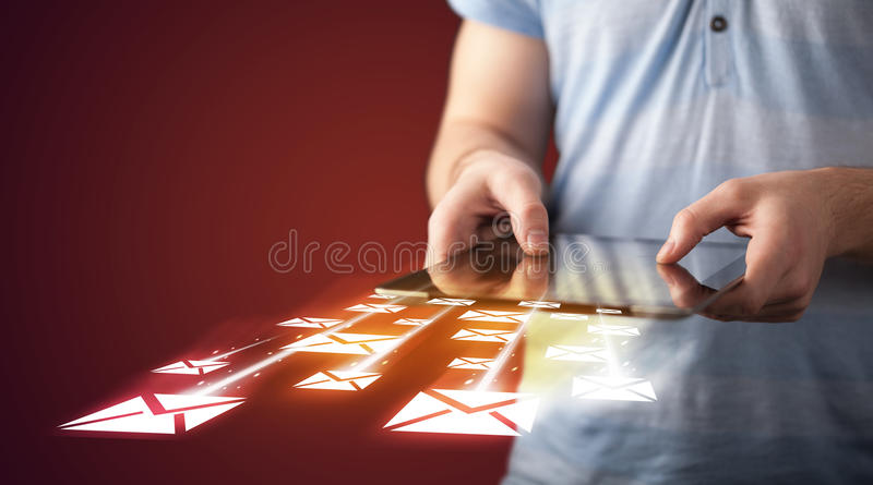 Hand holding tablet and sending email icons stock images