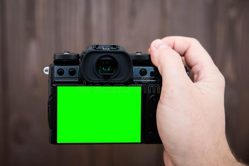 Hand holding and taking shot with green display mirrorless camera on wooden table.  stock image