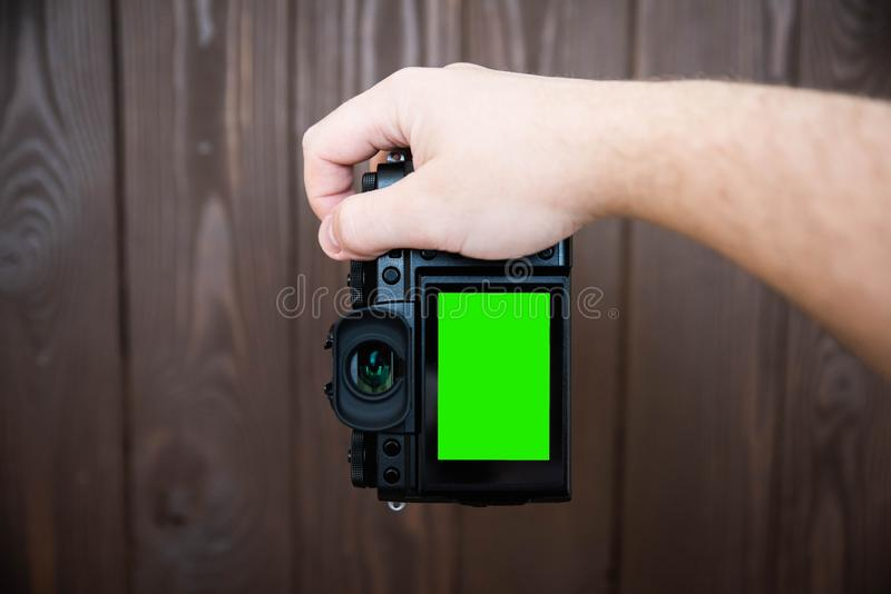 Hand holding and taking shot with green display mirrorless camera on wooden table.  royalty free stock image