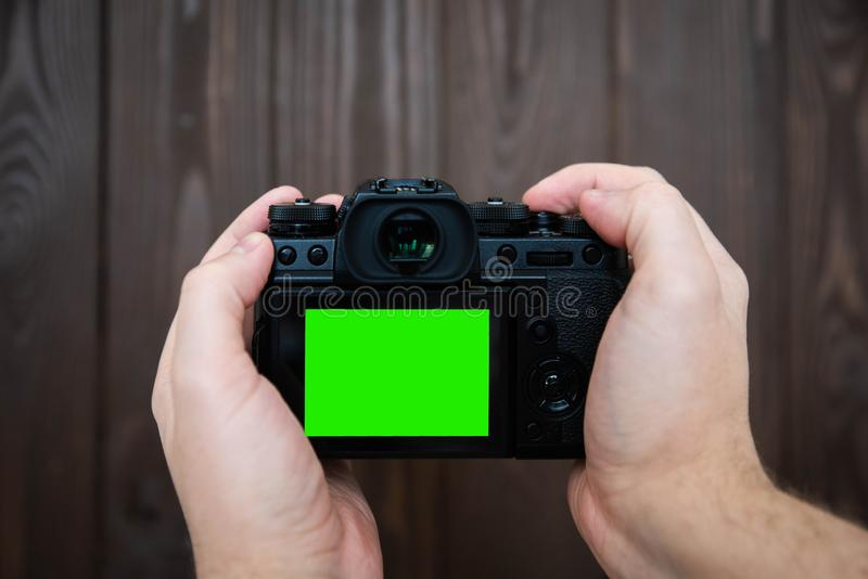Hand holding and taking shot with green display mirrorless camera on wooden table.  royalty free stock photography