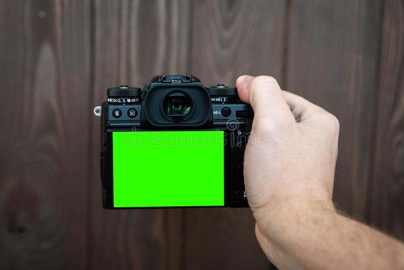 Hand holding and taking shot with green display mirrorless camera on wooden table.  royalty free stock photo