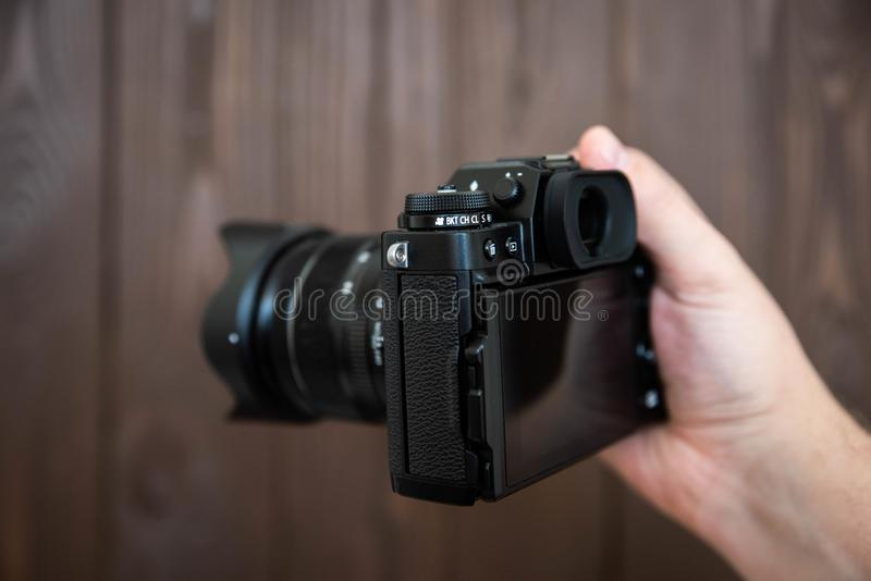 Hand holding and taking shot with green display mirrorless camera on wooden table.  stock photography