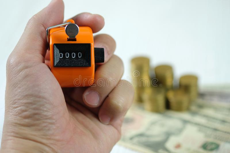 Hand holding tally counter or counting machine with 0000 number, step of coin stack on white wooden table, business and finance c stock image