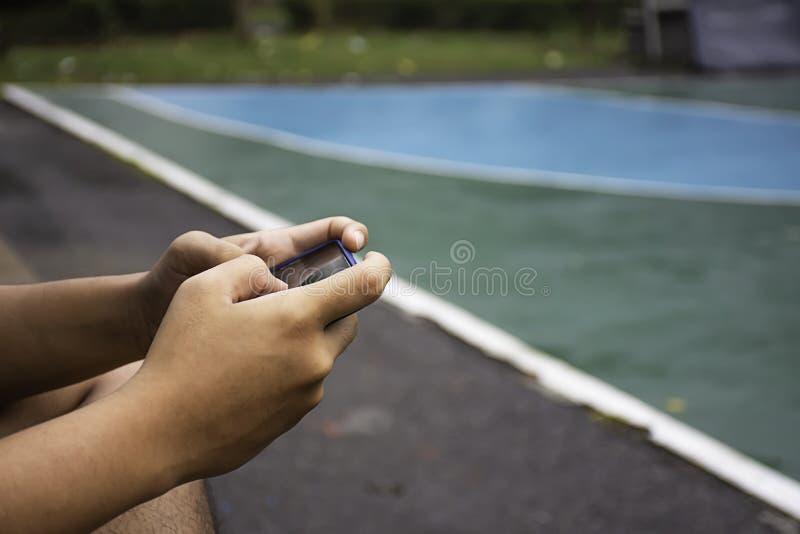 Hand holding telephone Background on basketball court stock image
