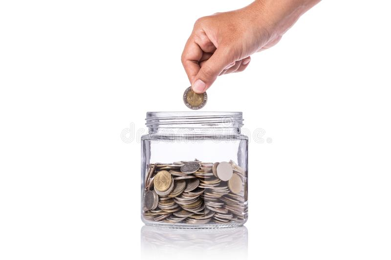 Hand holding Thai coin (baht) and insert to clear glass jar. Stu royalty free stock photography