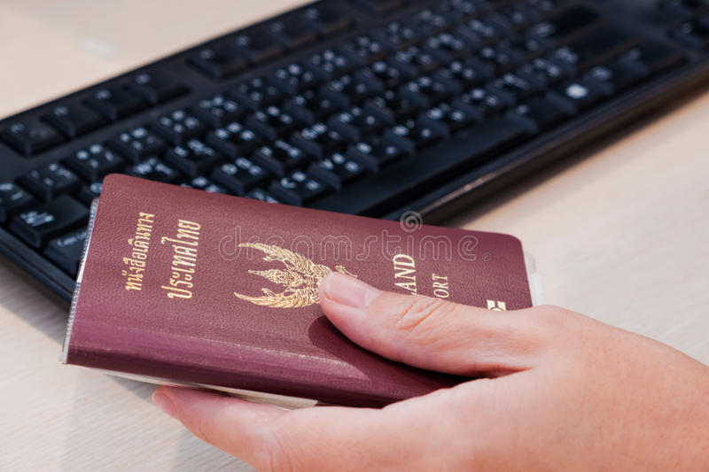 A hand holding Thailand passport besides keyboard. stock image