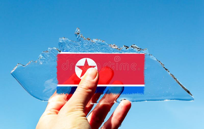 A hand holding thin transparent piece of ice in the shape of an iceberg with the flag of the North Korea, DPRK against a blue sky. A hand holding a thin stock images