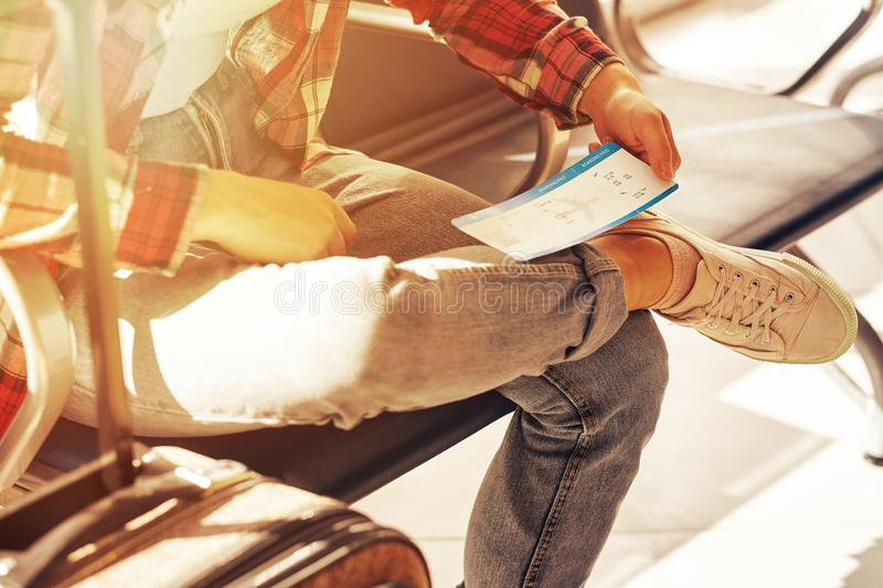 Hand holding tickets or boarding pass. Air travel at gate waiting in terminal stock images