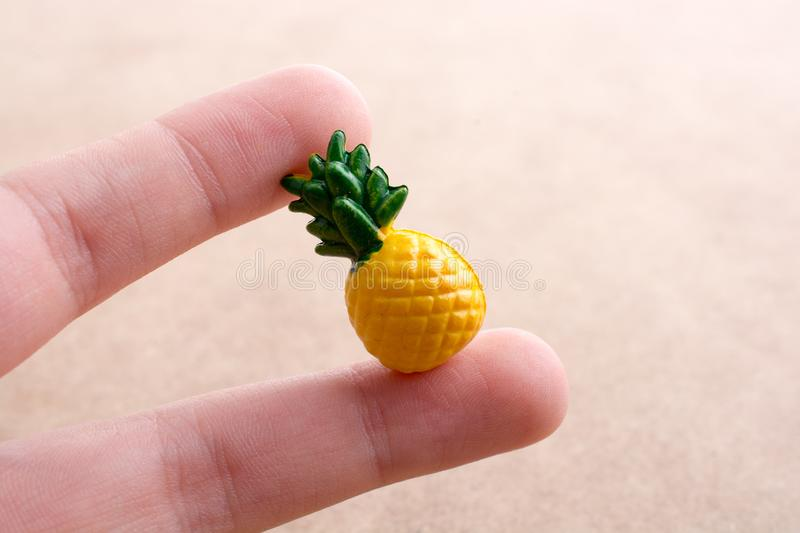 Hand holding a tiny pineapple miniature on a background royalty free stock photo