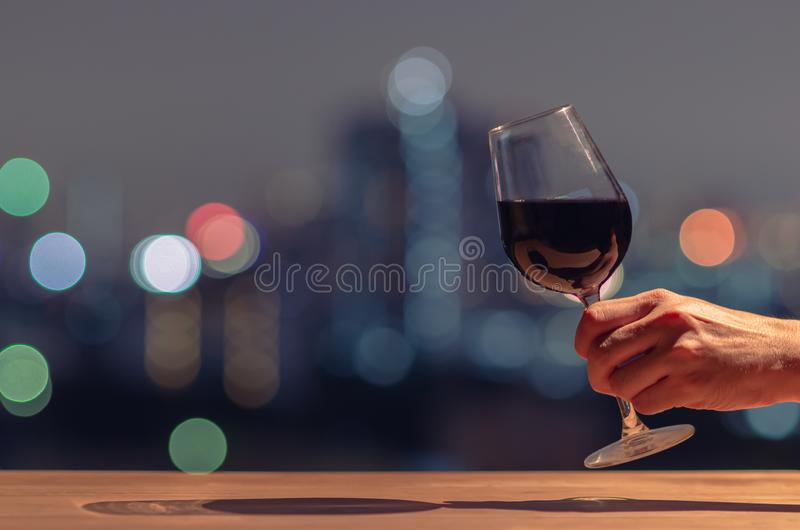 Hand holding and toasting a glass of red wine. stock photos