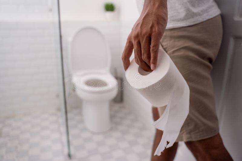 Hand holding toilet paper before using it royalty free stock photography