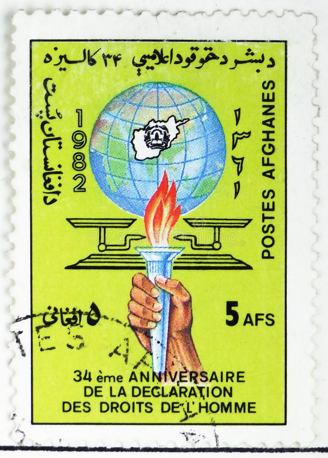 Hand holding Torch, Globe and Scales, 34th Anniversary of the Declaration of Human Rights serie, circa 1982. MOSCOW, RUSSIA - JULY 25, 2019: Postage stamp royalty free stock photo