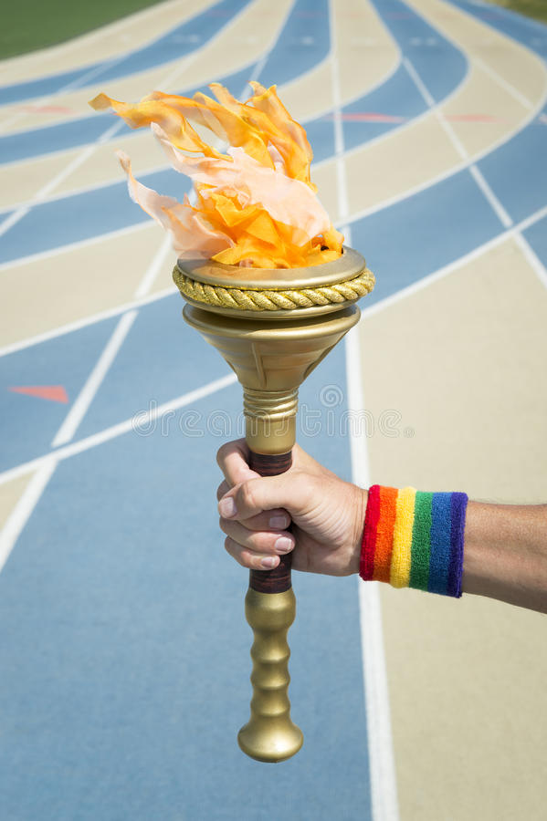 Hand Holding Torch Rainbow Wristband. Hand of an athlete wearing gay pride rainbow wristband holding sport torch in front of blue and tan running track stock photos
