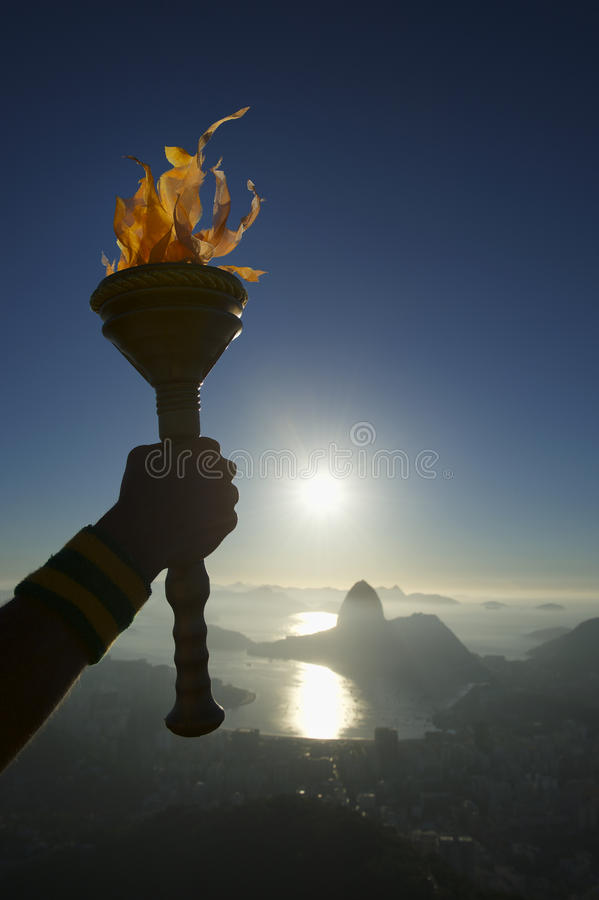 Hand Holding Torch Rio de Janeiro Brazil. Hand of an athlete holding sport torch in silhouette against Rio de Janeiro Brazil sunrise skyline with Sugarloaf royalty free stock photo