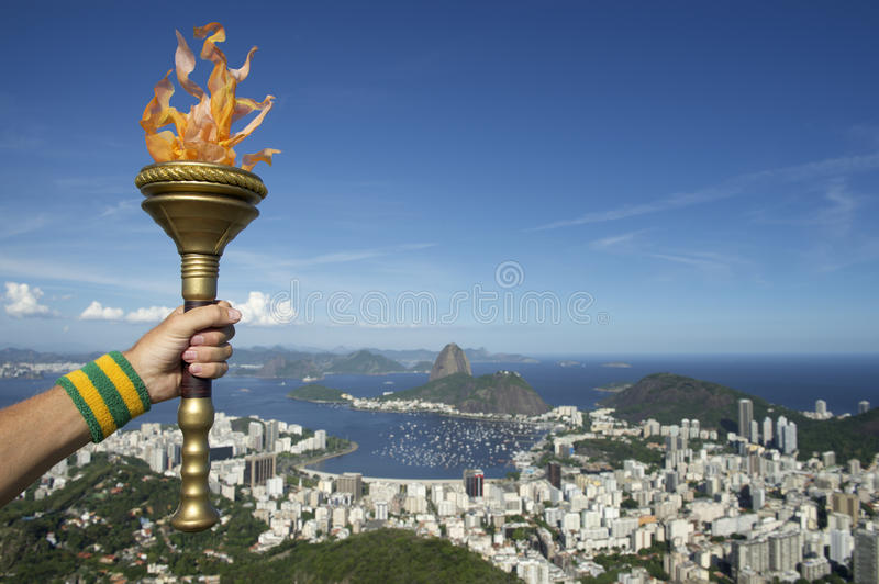 Hand Holding Torch Rio de Janeiro Brazil. Hand of an athlete wearing Brazil colors sweatband holding sport torch against Rio de Janeiro Brazil skyline with royalty free stock photos