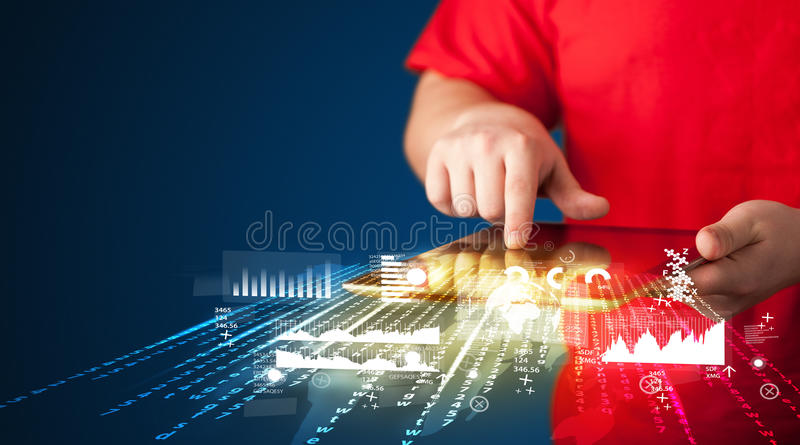 Hand holding touchpad tablet with business market graphs stock image