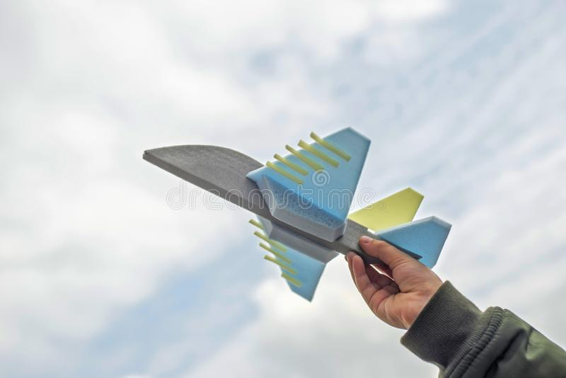Hand holding toy airplane in the sky. Toy airplane in hand - a symbol of travel and dreams stock photo