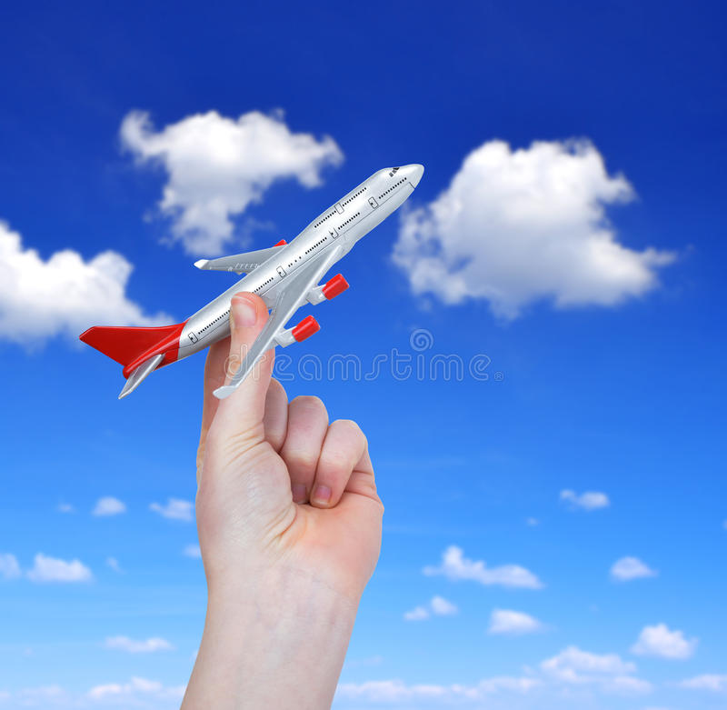Hand holding the toy plane. Against cloudy sky stock image