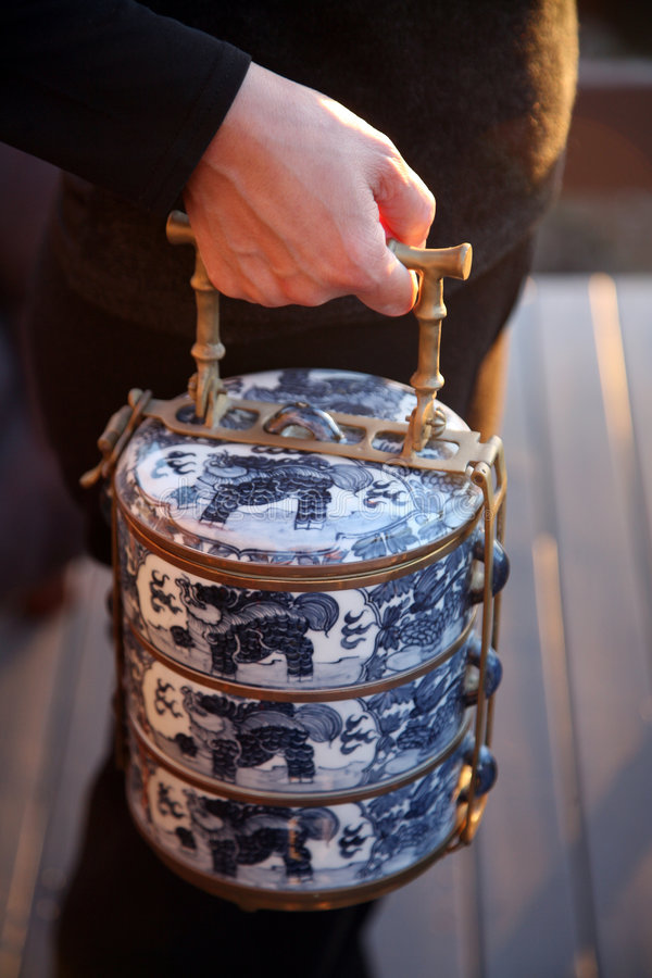 Hand holding traditional Asian food carrier stock image