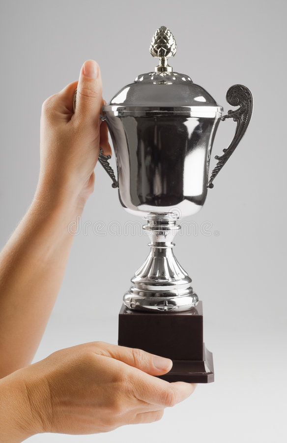 Hand holding trophy in victorious position