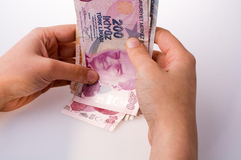 Hand holding Turksh Lira banknotes in hand. Hand holding Turksh Lira banknotes on white background royalty free stock photos