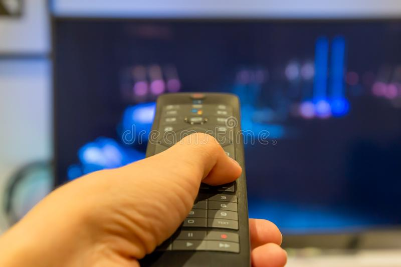 Hand holding TV remote control with a television in the background. Close up. Screen, media, technology, entertainment, button, press, home, push, people, flat royalty free stock photo