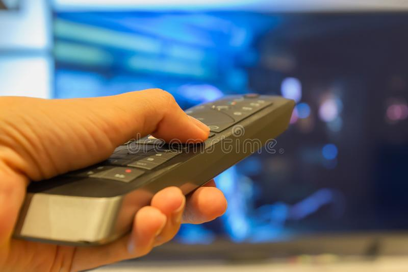 Hand holding TV remote control with a television in the background. Close up stock photo