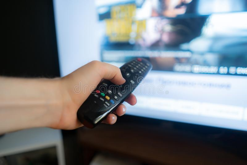 Hand holding a tv remote, swithing media chanels screens. Hand holding a tv remote, swithing media chanels screen stock photo