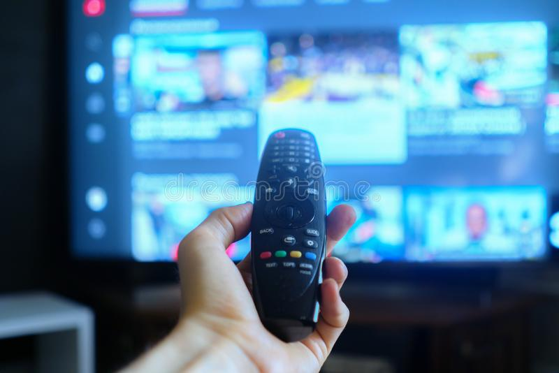 Hand holding a tv remote, swithing media chanels screens. Hand holding a tv remote, swithing media chanels screen stock image