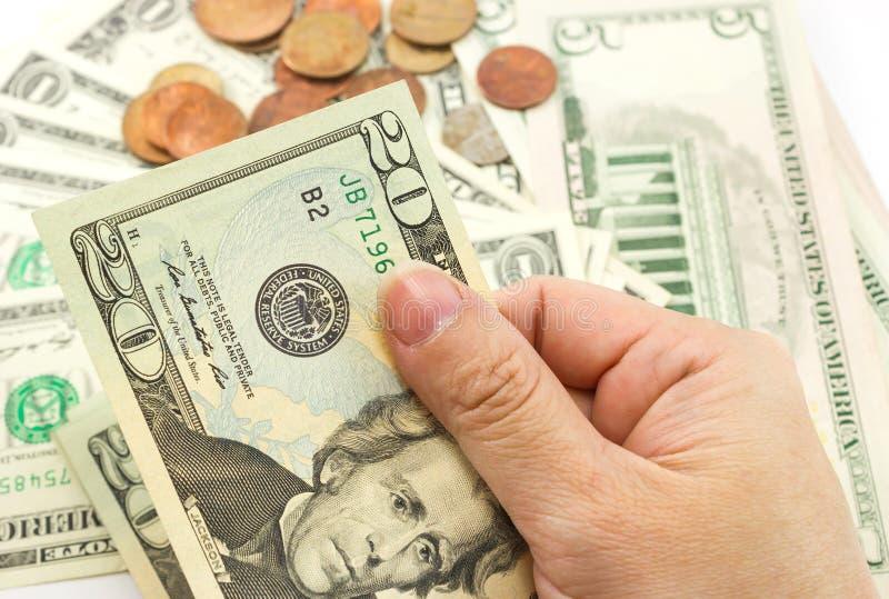 Hand holding a twenty dollar bill. Hand holding dollar bills with coins and dollar bill are background stock photos