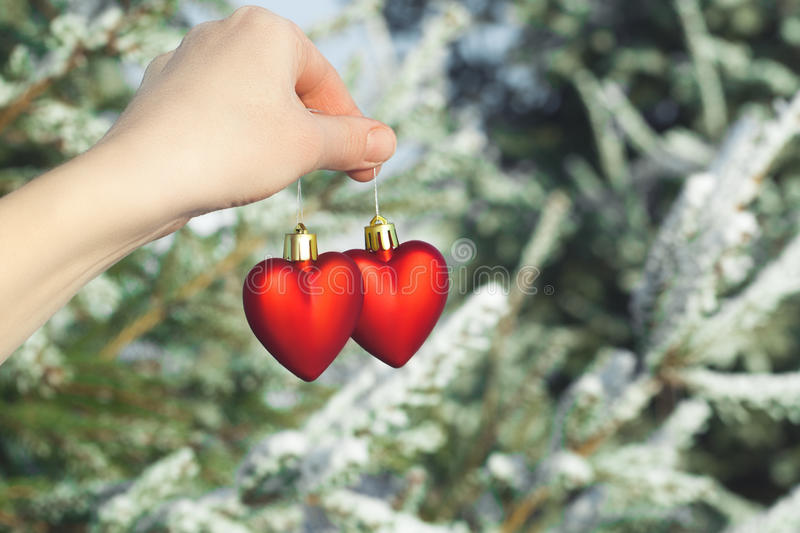 Hand holding two hearts outdoor over snowy pine trees. stock images