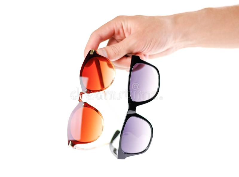 Hand holding two sunglasses. Men`s and women`s sunglasses. Close royalty free stock image