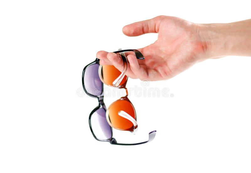 Hand holding two sunglasses. Men`s and women`s sunglasses. Close stock photos