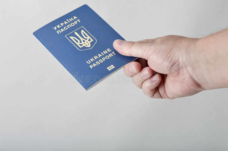 Hand holding Ukrainian biometric passport against white background. Closeup with copy space stock photos