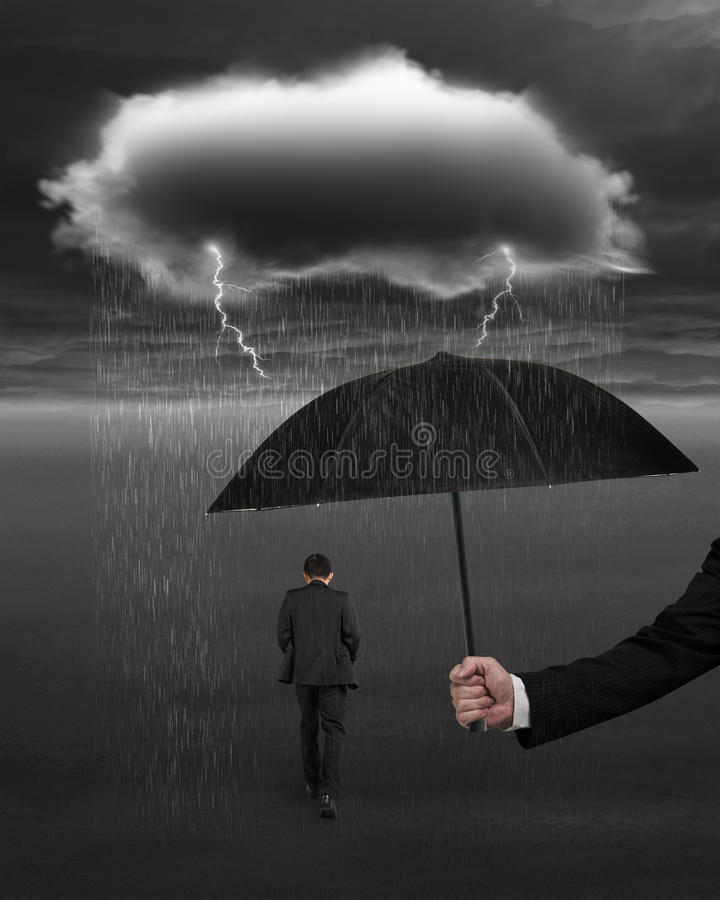 Hand holding umbrella protecting businessman from dark cloud rain lightning royalty free stock images