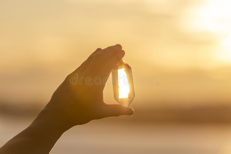 A hand holding up a beautiful quartz crystal outdoors in the sun.  royalty free stock photos