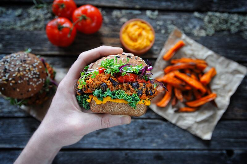 Hand holding vegan sweet potato black bean burger. Plant based food concept stock photography