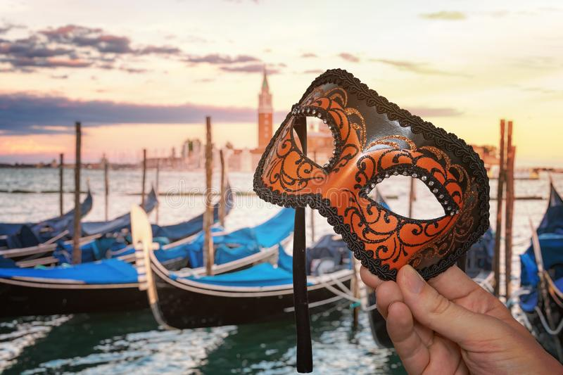 Hand holding Venetian carnival mask at traditional venetian festival in Italy. Gondolas in background. stock photos