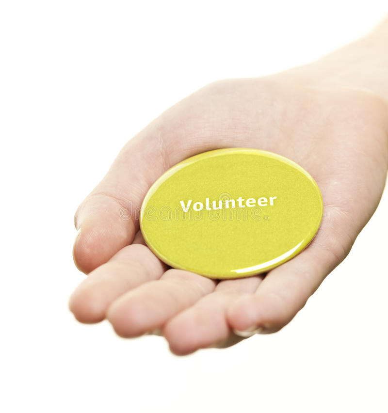 Hand holding volunteer button stock photo