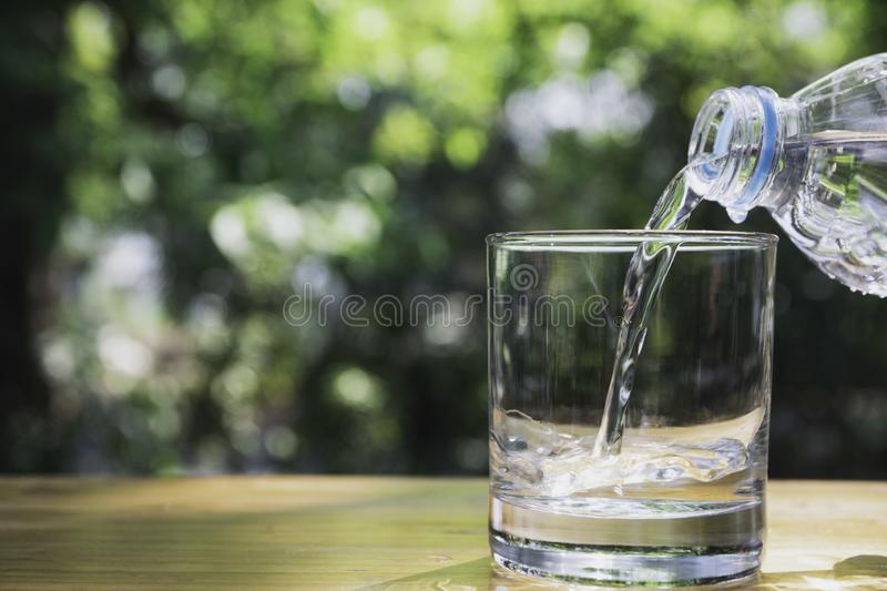 Hand holding water bottle on wooden in nature background.  royalty free stock photos