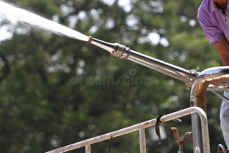 Hand holding water hose to prevent fire on car royalty free stock photos
