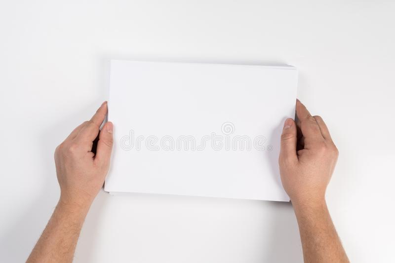 Hand holding white blank paper sheet mockup, . Arm in shirt hold clear brochure template mock up stock photos