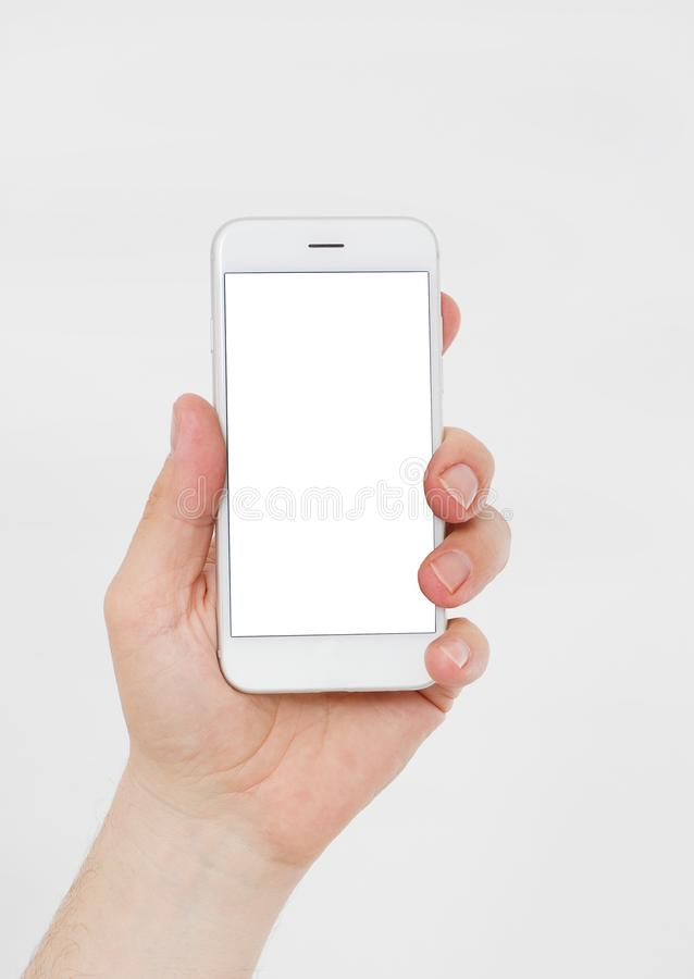 Hand holding white cellphone isolated on white clipping path inside. Online shopping. Top view. Mock up. Copy space. Template.Blan stock image
