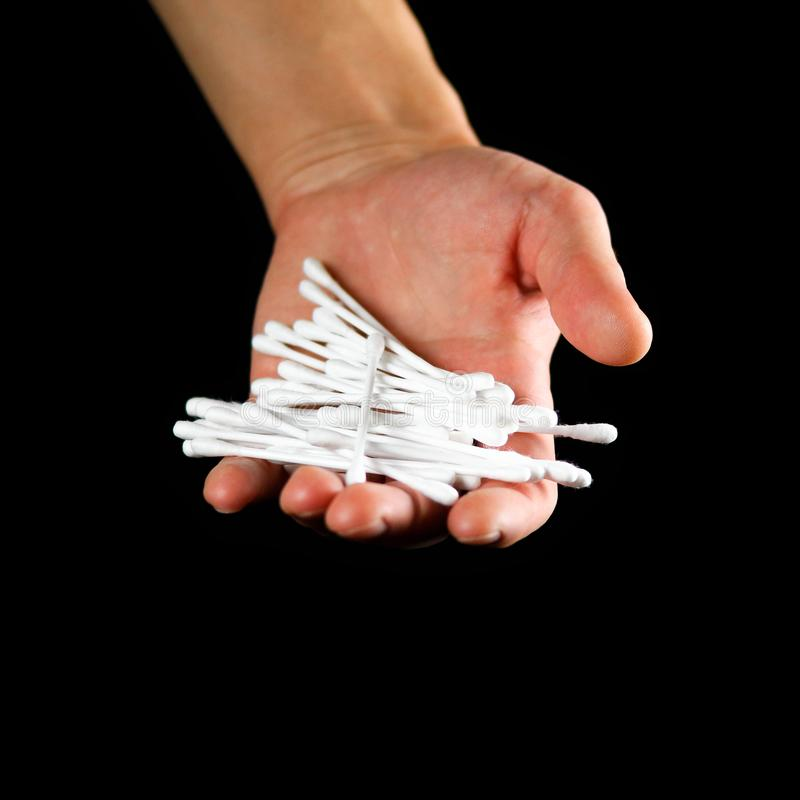Hand holding a white cotton swab. Close up. Isolated on black background stock photo